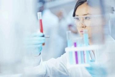 scientist analyzing test tube of medicine in laboratory