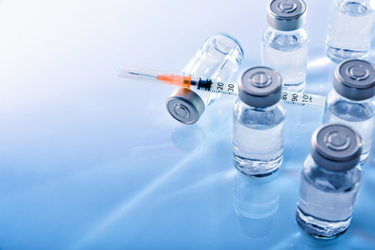 Vials and syringe on blue table top elevated.jpg