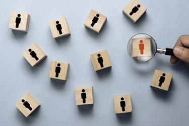 Hand holding magnifier glass hiring recruit