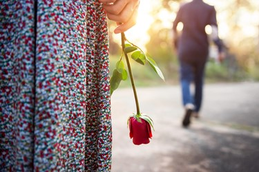woman holding rose man walking away