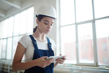 Female Engineer IN Hard Hat On Tablet